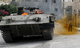 A PALESTINIAN BOYS THROWS A PETROL BOMB ON AN ISRAELI TANK DURING A MILITARY OPERATION IN JENIN