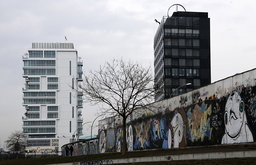 A luxury apartment building (L) is pictured beside sections at the East Side Gallery, the largest remaining part of the former Berlin Wall in Berlin