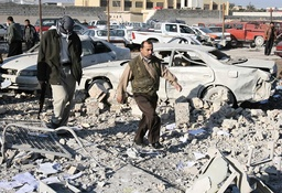 Police walk amid the rubble of a building of a police station after it was destroyed by British forces in Basra