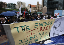 Lebanese and Palestinian refugees protest against recent Israeli air strikes in the Gaza Strip in front of the United Nation headquarters in Beirut