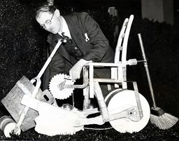 1934 Daily Mail Ideal Home Exhibition At Olympia. Inventor Heath Robinson Puts The Final Touches To A Combined Lawn-mower And Roller In The Garden Of His Whimsical House.