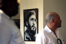 People walk near a photograph of former Cuban leader Fidel Castro at a gallery in Santiago de Cuba