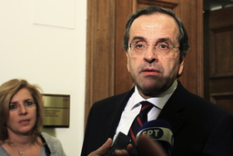 Greek Conservative leader Antonis Samaras talks to reporters in the parliament in Athens