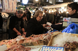A woman buys seafood at a food market in Athens