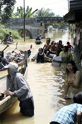 Villagers travel in boats through floodwaters in the village of Pelawi