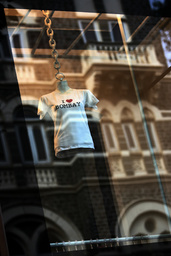 A t-shirt hangs in a garment shop as the Taj Mahal hotel is reflected on its window in Mumbai