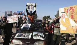 Residents carry posters of former Iraqi President Saddam Hussein during a protest in Tikrit