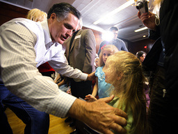 Republican presidential candidate and former Massachusetts Governor Romney greets two girls in the audience at a campaign stop in Council Bluffs