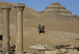 Men walk near the site of two recently discovered tombs in Saqqara