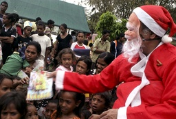 East Timorese President Xanana Gusmao, wearing a Santa Claus costume, gives presents to children during the celebration of Christmas at his home in Balibar