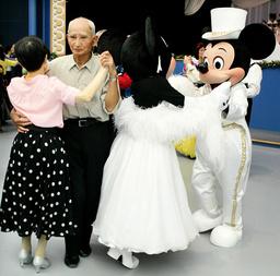 ELDERLY COUPLE DANCES NEXT TO MICKEY AND MINNIE MOUSE AT TOKYO DISNEYLAND IN URAYASU