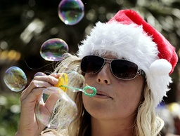 Jane Simmonds of England wears a Santa Claus hat as she blows bubbles during Christmas Day at Shelley Beach in Sydney