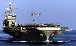 US NAVY HELICOPTER CARRIES CARGO ONTO THE CARL VINSON