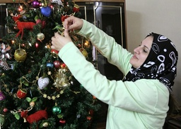 Woman decorates Christmas tree in her house in Baiji