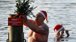 A members of Berlin's ice swimming club Berliner Seehunde places a fir branch on a pole in Orankesee lake in Berlin