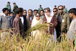 Khaleda Zia, chairperson of BNP and former PM, talks to farmer holding sheaf of paddy, party's election symbol, in Tangail