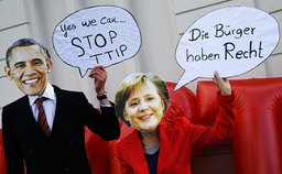 Protesters wear masks of U.S. President Obama and German Chancellor Merkel to demonstrate against TTIP free trade agreement before the opening ceremony of the Hannover Messe in Hanover
