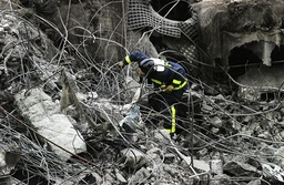 Fireman inspects the rubble at one of the parking lots of Madrid's Barajas airport
