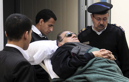 Former Egyptian president Hosni Mubarak lies on a gurney bed while leaving the courtroom at the police academy in Cairo